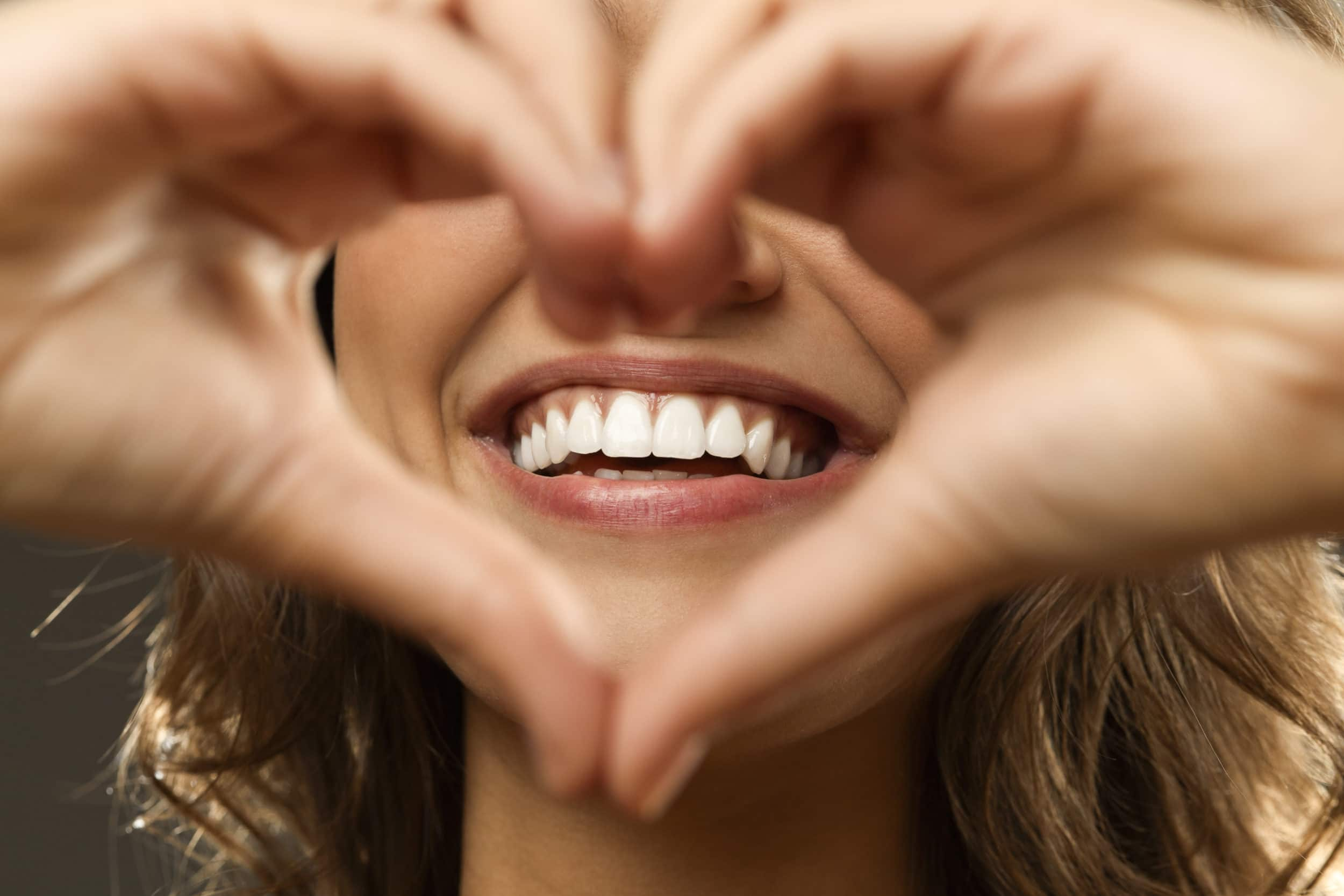 Woman smiling with hands gesturing a heart